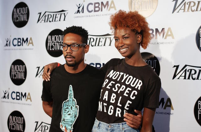 Black man in black t-shirt with teal logo next to Black woman in black t-shirt with white text and blue jeans in front of white screen with black text and images