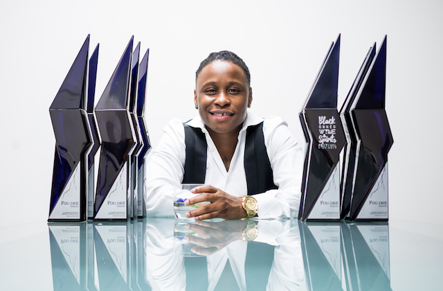 Black woman in white dress shirt and black vest sits behind green glass table with purple alcohol bottles while holding clear glass with clear beverage and green lime in front of light grey wall