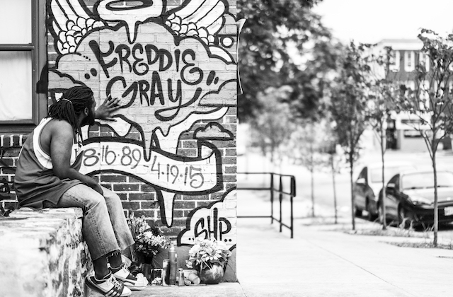 Black-and-white photo of Black man in jeans, tank top and sneakers with hand on mural on brick wall while sitting on stone ledge in front of grey sky