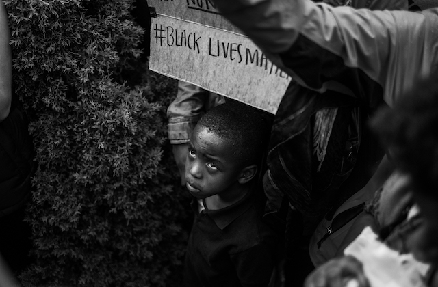 Black-and-white photo of Black child in dark sweater in front of Black adult in jacket holding grey sign with black text in front of bush