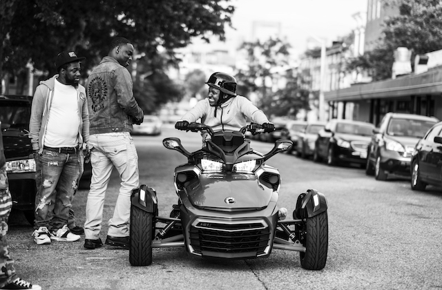 Black-and-white photo of two Black boys standing near a Black boy sitting on a multi-colored all-terrain vehicle with black helmet on grey street