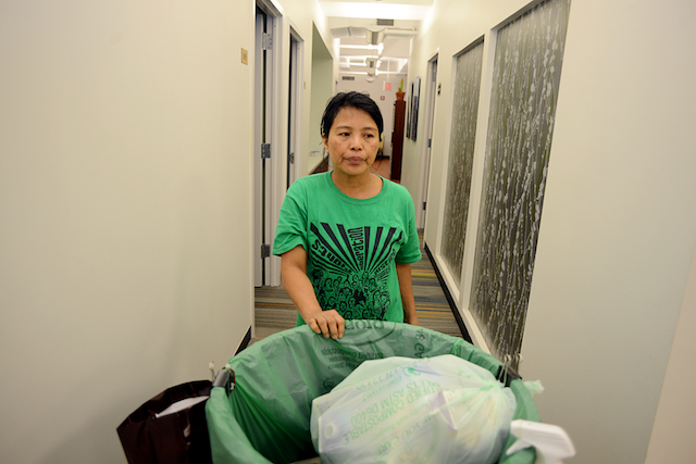 An Asian woman wearing a green t-shirt pushes a trash can down a hallway.
