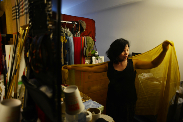 An Asian woman in a small room puts on a yellow scarf