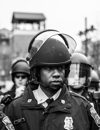 Black-and-white photo of Black man in black police uniform and riot gear in front of other policemen and grey sky