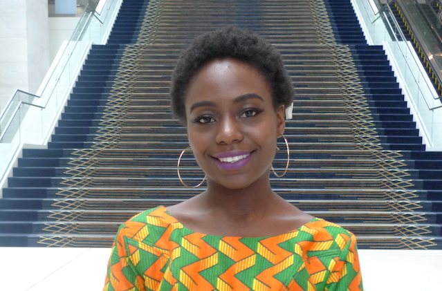 A young Black woman with a medium-length afro and a yellow, orange and green African wax print dress poses at the end of a staircase.