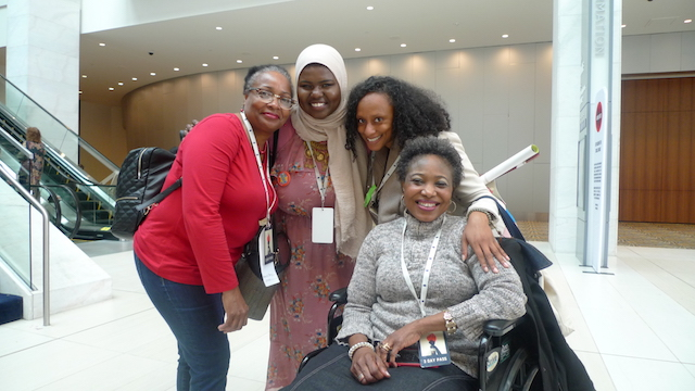 Four Black and Brown women of various ages pose at the Women's Convention