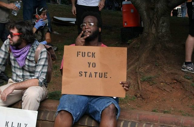 A Black man sits down and smokes while holding a sign that says