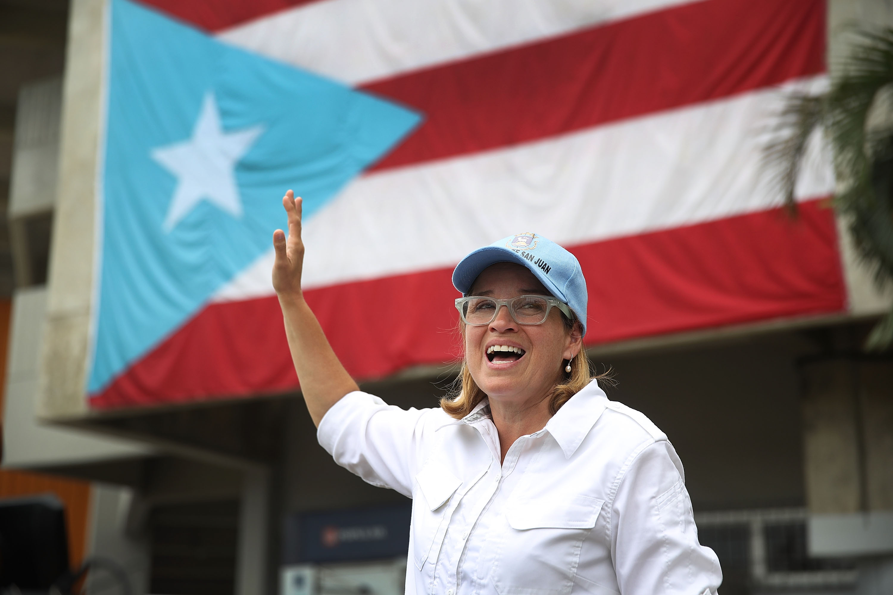 Carmen Yulin Cruz wearing a hat waves in front of a Puerto Rican flag
