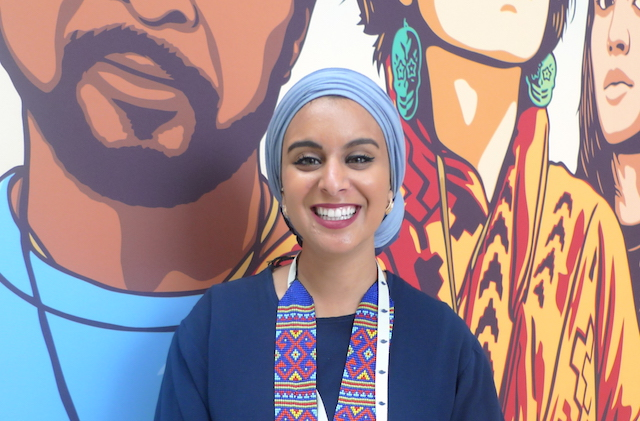A young woman in a light blue hijab and a multicolored necklace stands in front of a mural