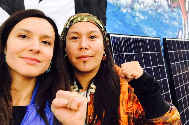 A Lubicon Cree woman with long black hair wearing a blue coat and a SecwepemcNation woman wearing a bandana and a septum ring stand in front of solar panels.