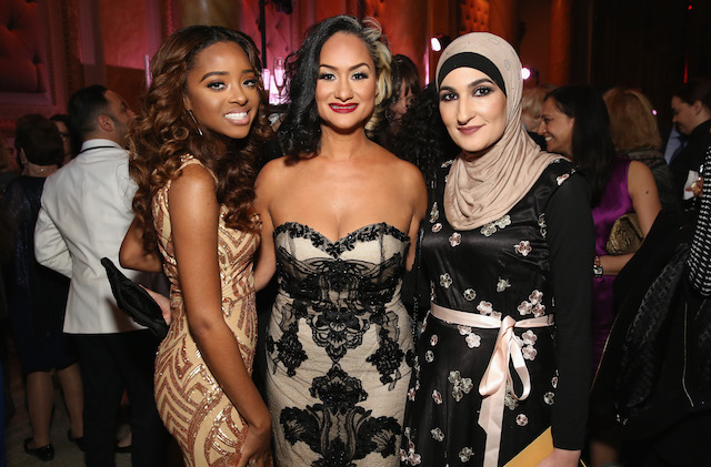 Three women in fancy dresses pose for a photo at a gala