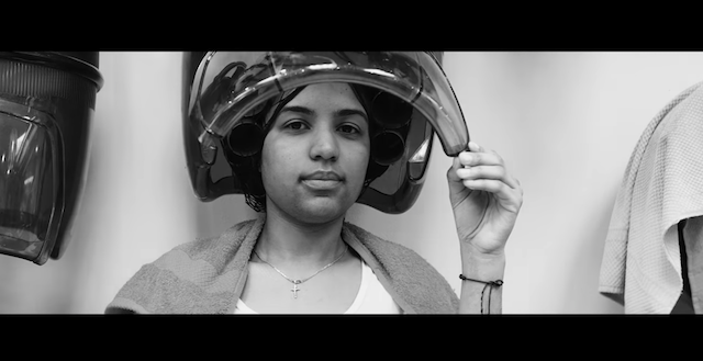 A Brown woman wearing rollers and a cross sits under a hair dryer