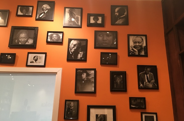 An orange wall with black and white photos of Black authors