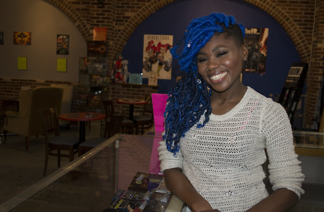 Black woman with blue dreadlocks in white shirt smiles in front of glass counter and brown walls and red chairs with multicolored artowkr