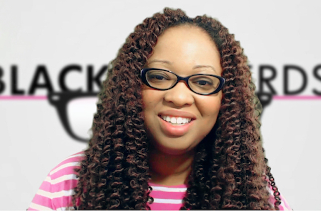 A Black woman with spiral curls and a pink and white striped shirt smiles in front of a backdrop