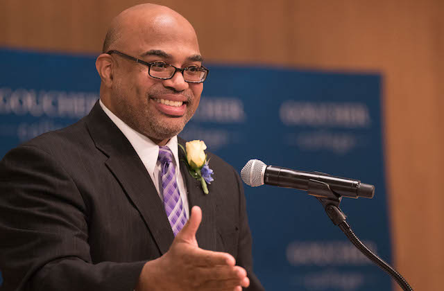A Black man wearing glasses, a navy blue suit and pink tie speaks at a lecturn