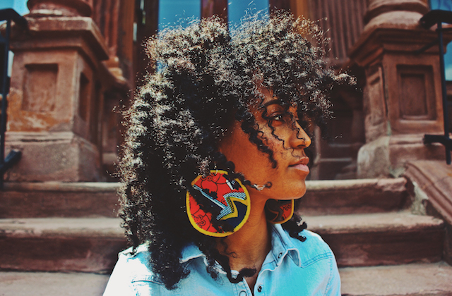 A Black woman with a long afro and large hoop earrings