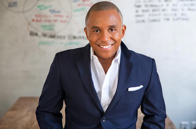 A Black man wearing a navy jacket smiles in front of a whiteboard with writing on it