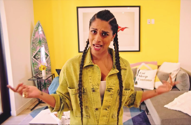 Lilly Singh. Asian-Canadian woman in yellow denim overalls and cornrows