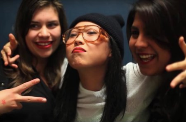 Awkwafina. Asian-American woman wearing black skullcap, white shirt and amber glasses, throws up two peace signs with arms around two brown-haired White women