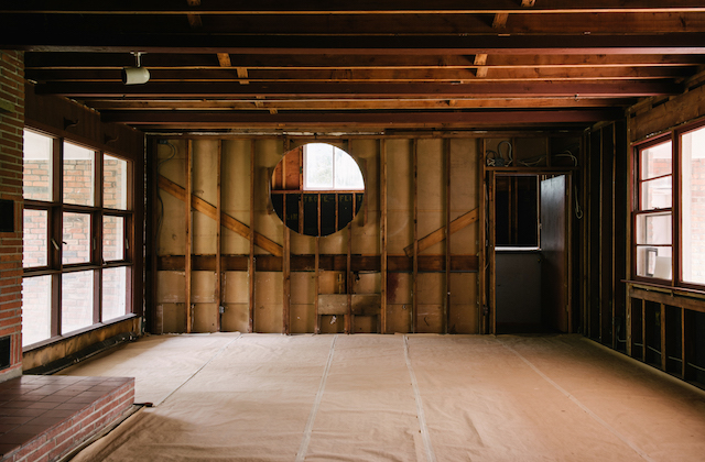 Brown house interior and exposed wood supports in room with circle cut out of one wall