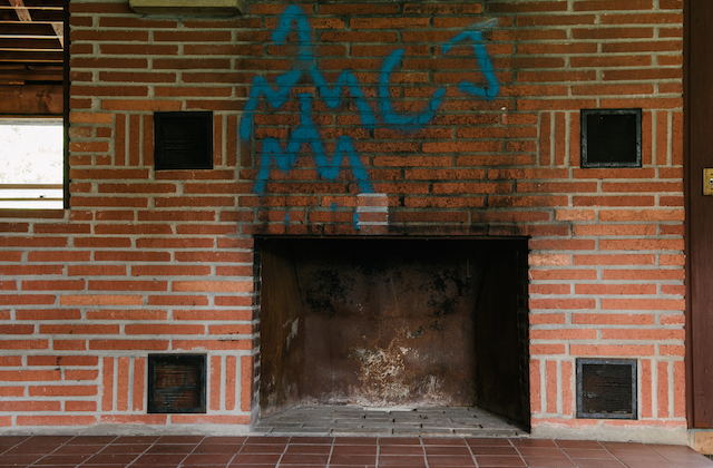 Red brick fireplace with blue graffiti overhead