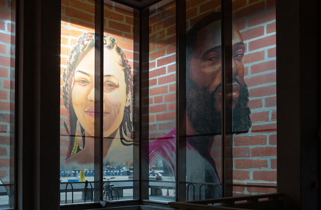 Portrait of Black woman in pink clothing on red brick background next to portrait of Black man in green clothing on grey and brown building interior