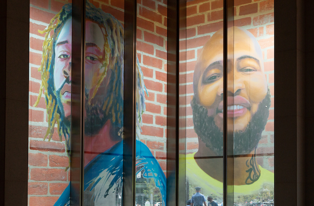 Portraits of Black men in blue and green clothing on red brick background on window of brown and grey building