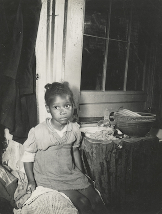 Black-and-white image of Black girl on bed in front of window