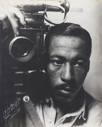 Gordon Parks. Black-and-white image of Black man holding camera in front of plain background