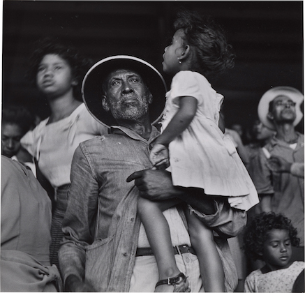 Black-and-white image of Latinx man holding Latinx girl in front of crowd and wall