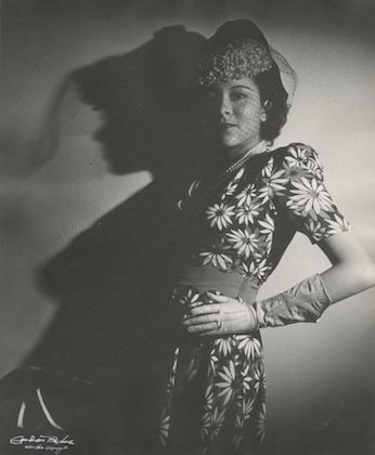 Marva Trotter Louis. Black-and-white image of Black woman in patterned dress and hat in front of plain wall.
