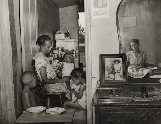 Sepia image of elderly Black woman seated with three grandchildren and near another Black woman in house.