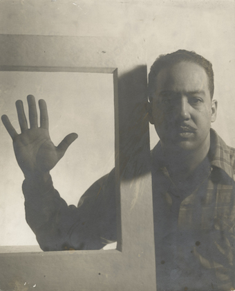 Langston Hughes. Sepia image of Black man wearing plaid shirt with hand in wooden frame in front of plain background