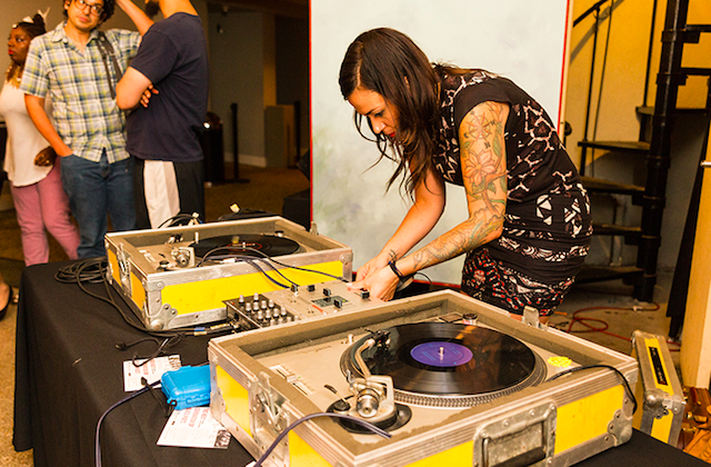 Marissa Johnson-Valenzuela. Brown woman in black and white dress with multicolored tattoos DJs behind black records and brown and yellow turntables on black table in front of white and yellow walls and people in multicolored clothes
