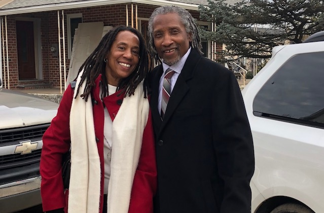 A Black man with gray locs wearing a suit and a Black woman with locs wearing a red coat stand together
