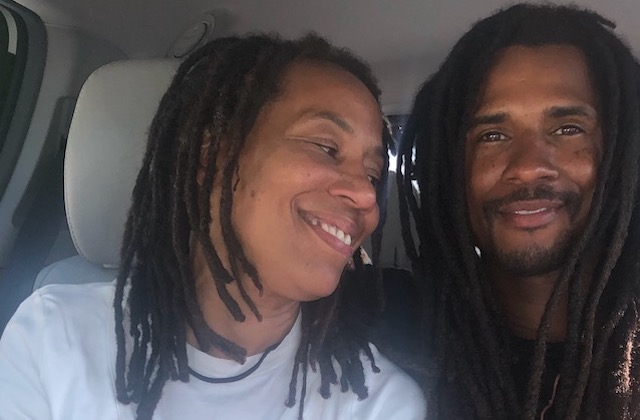 A Black man with long locs smiles at his mother who also has long locs