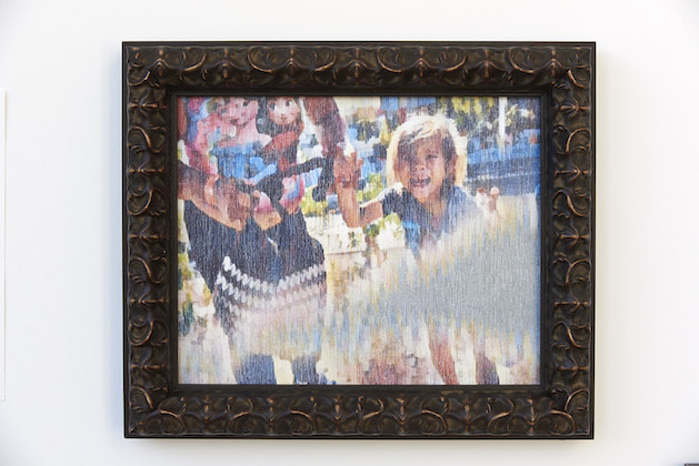 Photo of illustration of Latinx woman and girl crying in multicolored clothing in front of brown sand and multicolored border structures in brown frame on brown wall