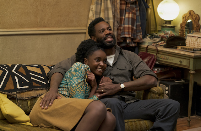 KiKi Layne and Colman Domingo. Black woman in green and brown shirt and brown skirt embraced by Black man in brown shirt and gray pants while seated on brown couch with yellow pillow and black and brown and white cover in front of brown wall and desk