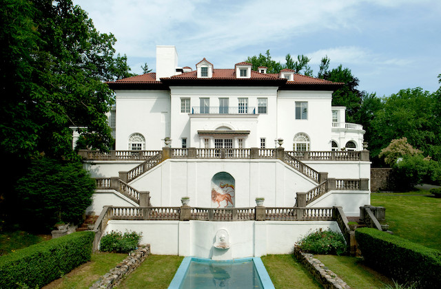 White mansion with brown roof and handrails and green trees and lawn and blue pool in front of blue sky