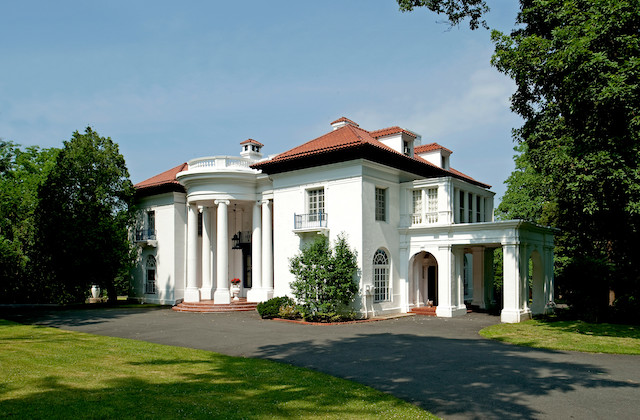 White mansion with brown roof and green trees and lawn and gray pavement in front of blue sky