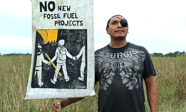 A young Native man with an eye patch holds up a sign that says