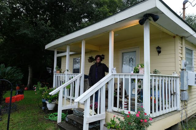 An elderly Black woman stands on the porch of a yellow shingled house.
