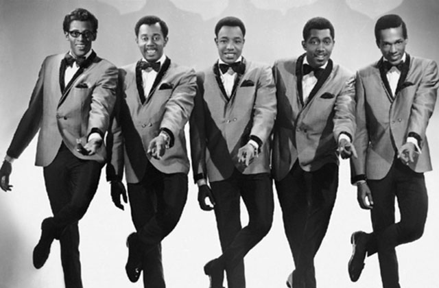 The Temptations. Five Black men in tuxedos with bowties in synchronized dance move.