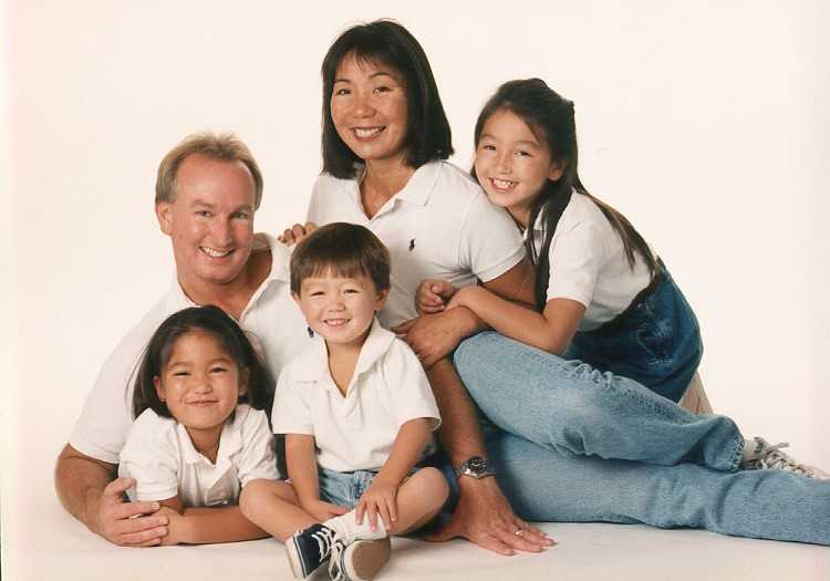 A Japanese woman poses with her White husband and their three children