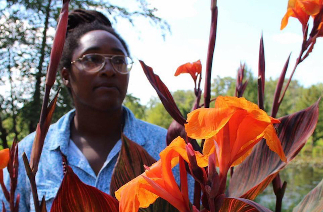 A Black women with a bun stands in a field with orange flowers.