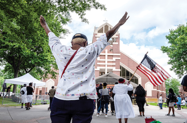 A Black person holds their hands in the air at the funeral service for Rayshard Brooks in Atlanta.