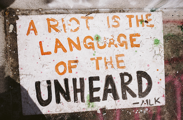 A sign reads 'Riots are the language of the unheard.""