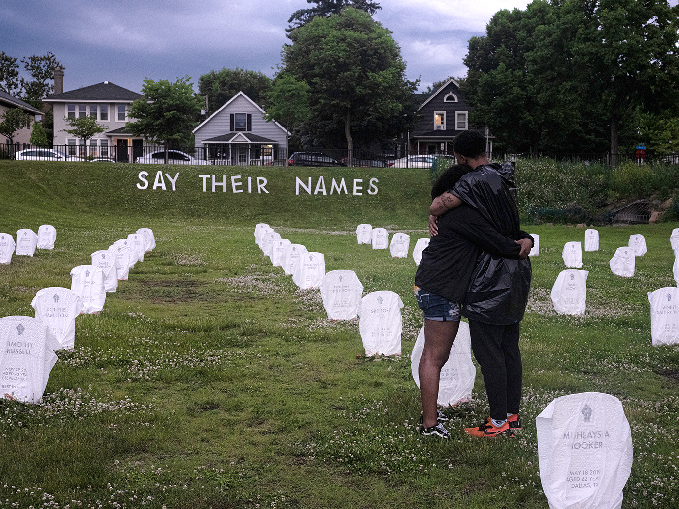 Two friends console each other amongst mock headstones at a makeshift memorial in Minneapolis for people who have been killed by police.