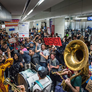 A brass band plays before a crowd in an airport terminal